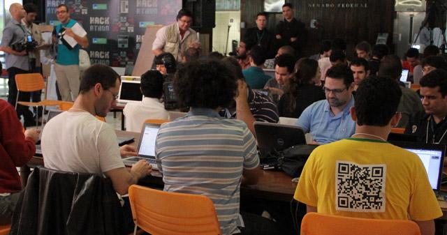 Diversas pessoas sentadas a mesas, desenvolvendo seus aplicativos.