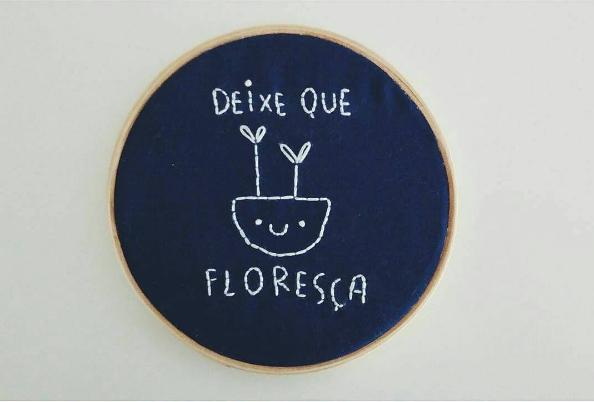 Bastidor com bordado branco em fundo azel escuro com desenho de um vazinho sorridente com plantinhas escrito - deixe que floresça